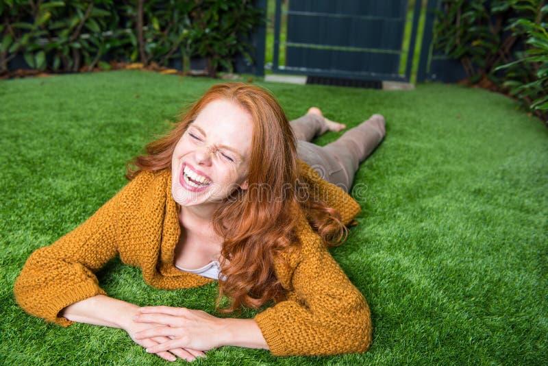 Красивая рыжеволосая женщина лежит на лужайке и принимает удовольствие стоковое изображение
