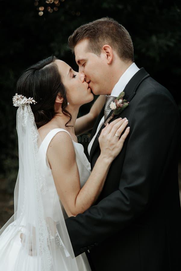 Красивая свадьба изумляя пар в парке, нежно обнимать и целовать стоковое изображение