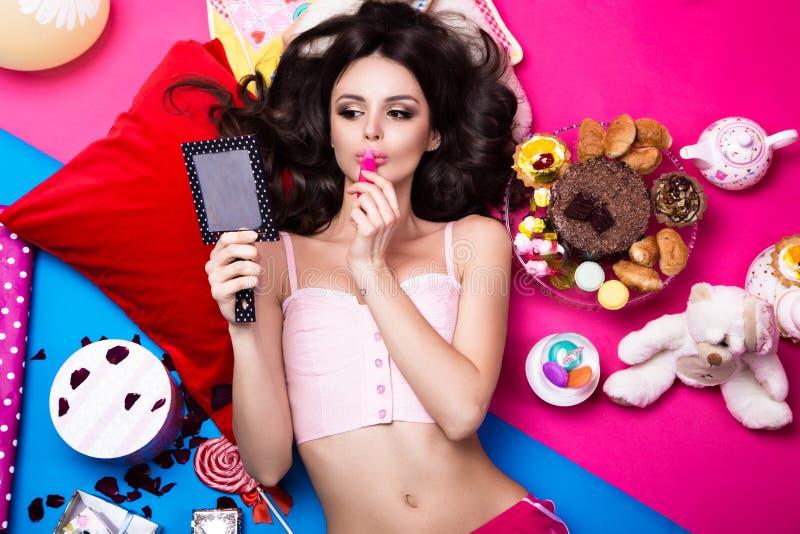 Красивая свежая кукла девушки лежа на ярких предпосылках окруженных помадками, косметиками и подарками Стиль красоты моды стоковая фотография rf