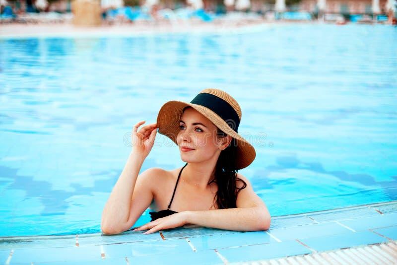 Красивая сексуальная девушка со здоровой кожей в элегантном Striped бикини, шляпе Солнца ослабляя в плавании стоковое фото rf