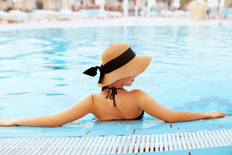 Забота тела женщины лета Красивая сексуальная девушка со здоровой кожей в элегантном Striped бикини, шляпе Солнца ослабляя в басс стоковое фото rf