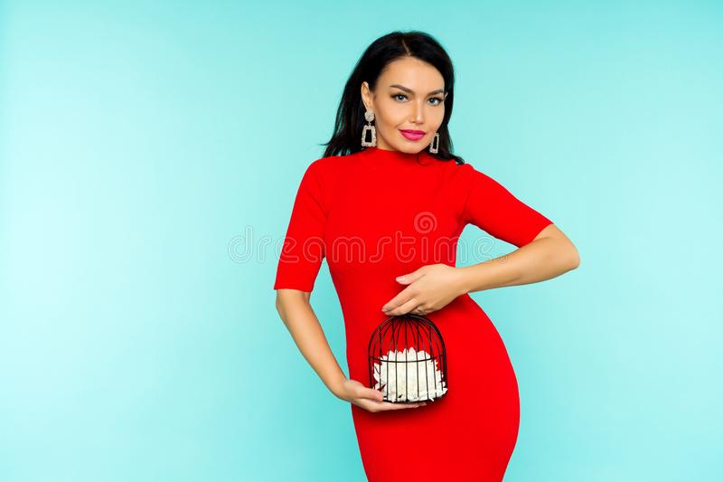 Красивая сексуальная женщина брюнета в красном платье держа клетку птицы с внутренностью цветка на голубой предпосылке стоковая фотография