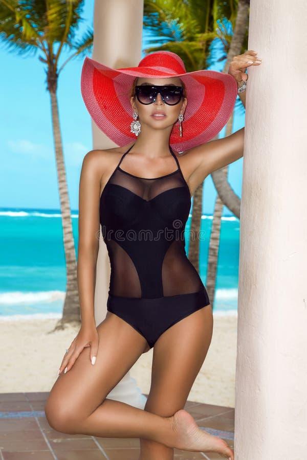 Красивая, сексуальная женщина в бикини и шляпа, представляя на карибском пляже стоковое изображение rf