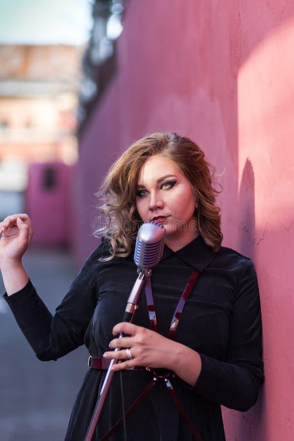 Красивая сексуальная женщина поя с микрофоном стоковое фото