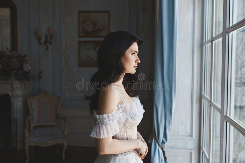 Красивая, сексуальная и чувственная девушка модели брюнет в стильном платье шнурка при нагие плечи представляя в роскошном годе с стоковое изображение rf