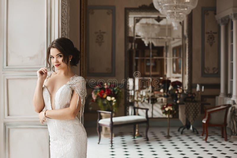Красивая, сексуальная и чувственная девушка модели брюнет с ярким составом и модным стилем причёсок, в стильные усмехаться платья стоковое фото