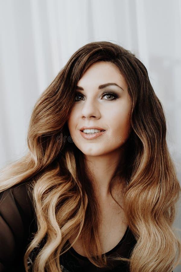 Красивая сексуальная коричневая курчавая длинная женщина волос представляя в кровати стоковые изображения