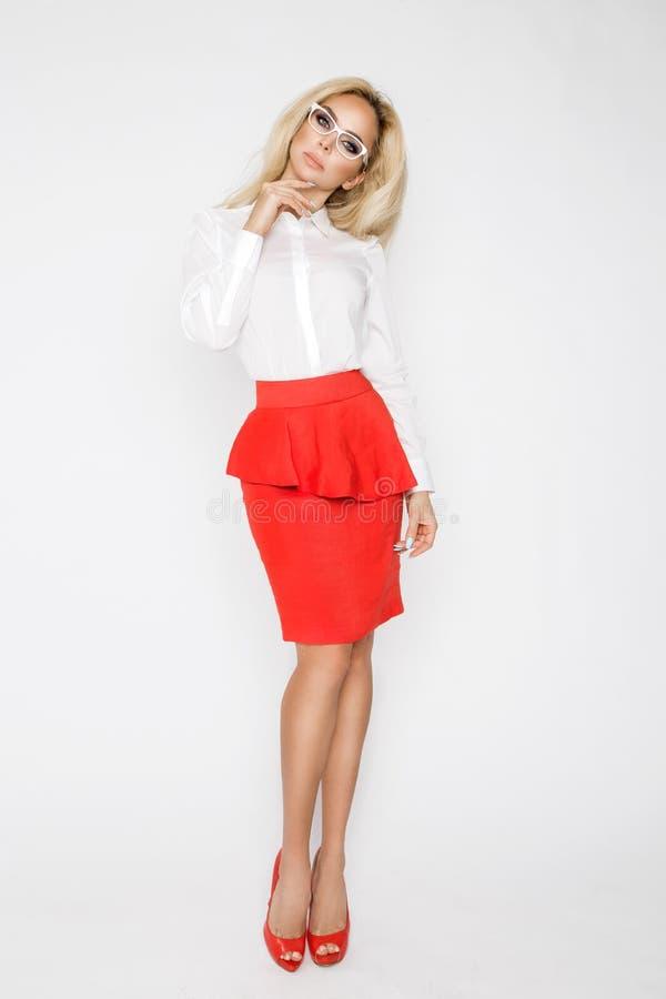Красивая, сексуальная, элегантная белокурая женская модель в белой рубашке и красная юбка стоковая фотография