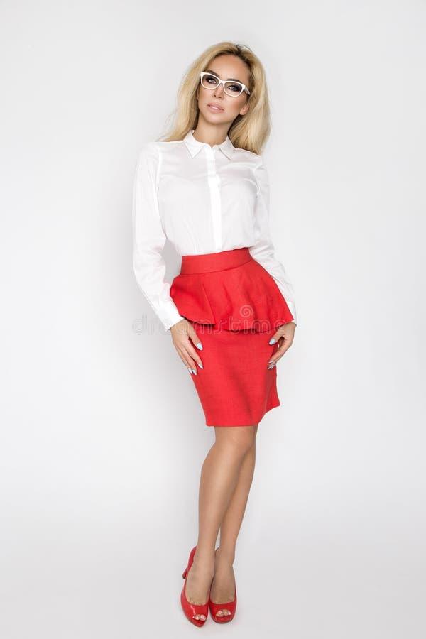 Красивая, сексуальная, элегантная белокурая женская модель в белой рубашке и красная юбка стоковые изображения
