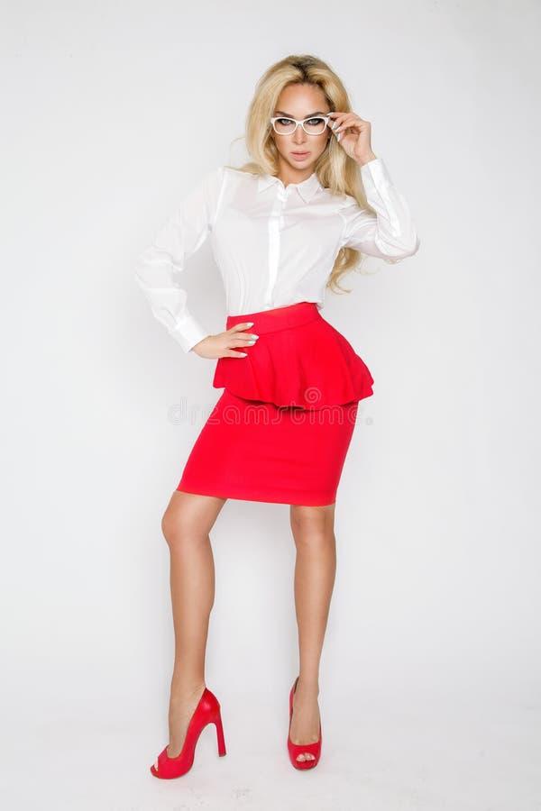 Красивая, сексуальная, элегантная белокурая женская модель в белой рубашке и красная юбка стоковые изображения rf