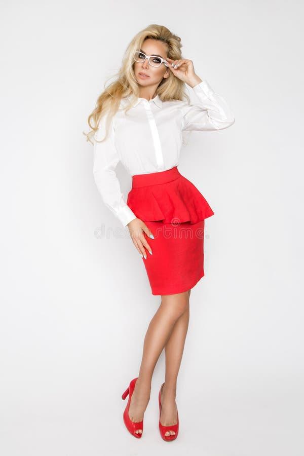 Красивая, сексуальная, элегантная белокурая женская модель в белой рубашке и красная юбка стоковые фотографии rf