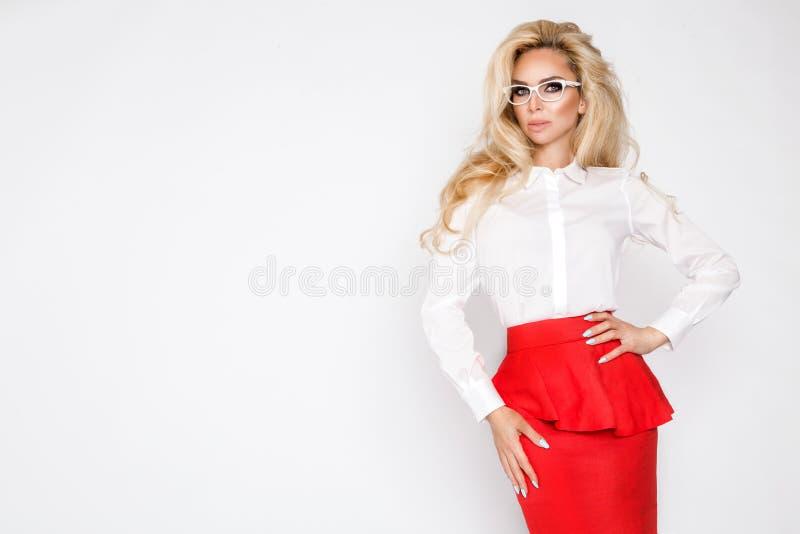Красивая, сексуальная, элегантная белокурая женская модель в белой рубашке и красная юбка стоковое фото rf