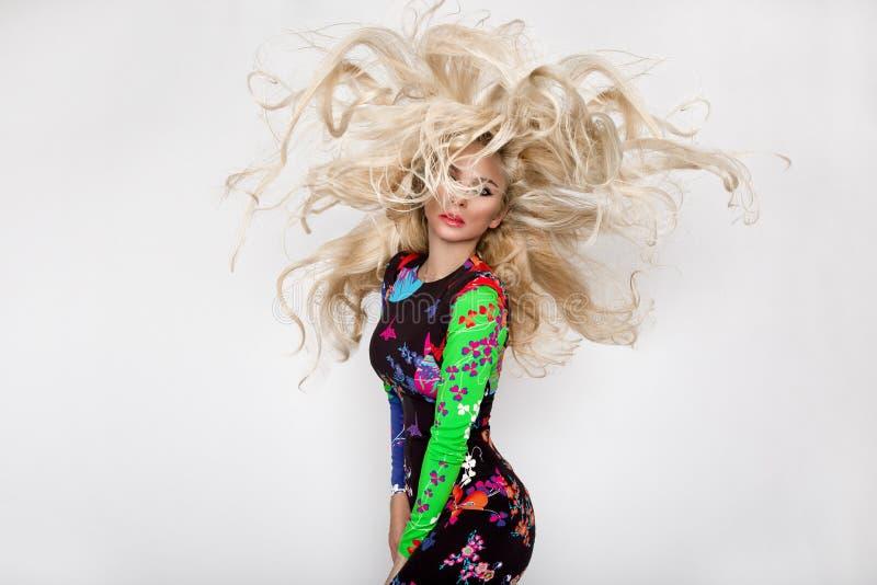 Красивая сексуальная белокурая модель с изумляя глазами, волосы тома ветра вниз длинные с самыми интересными, и датчики улучшают  стоковое фото