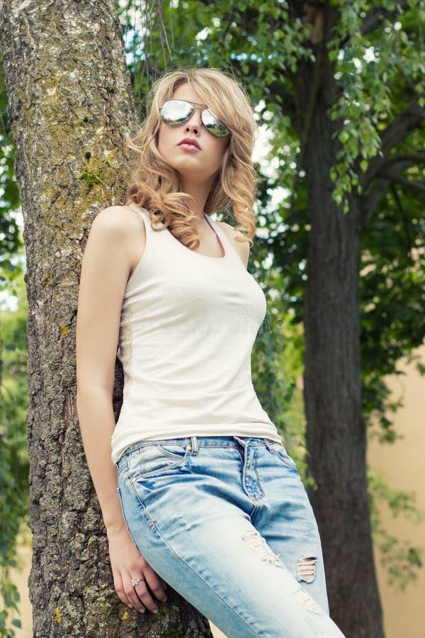 Красивая сексуальная блондинка девушки в парке в солнечных очках при большие толстенькие губы стоя около дерева стоковое изображение rf