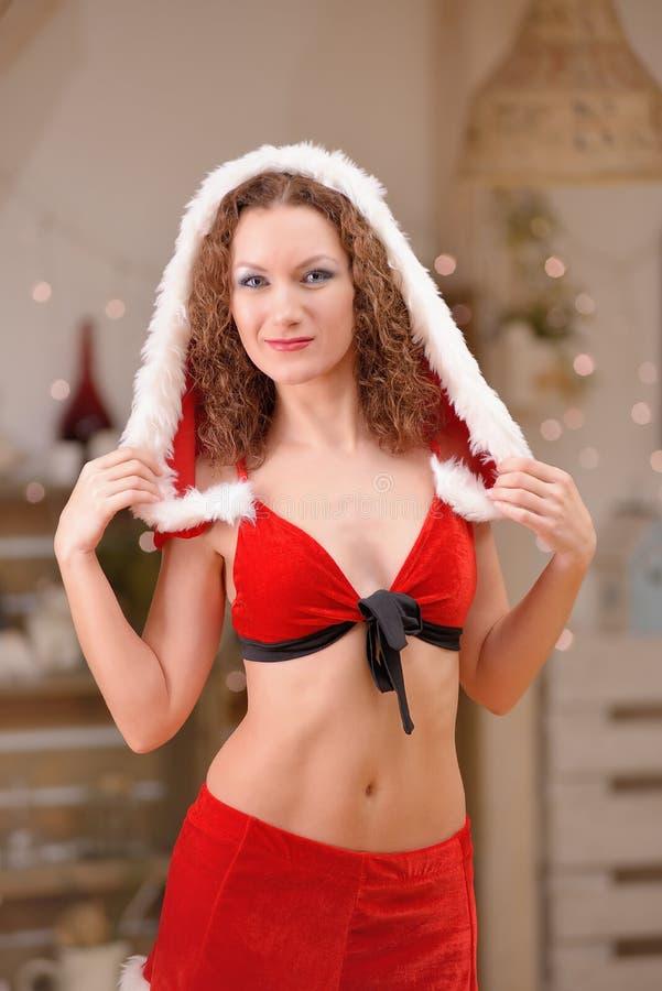 Красивая сексуальная девушка с вьющиеся волосы в Санта Клаусе одевает стоковая фотография rf