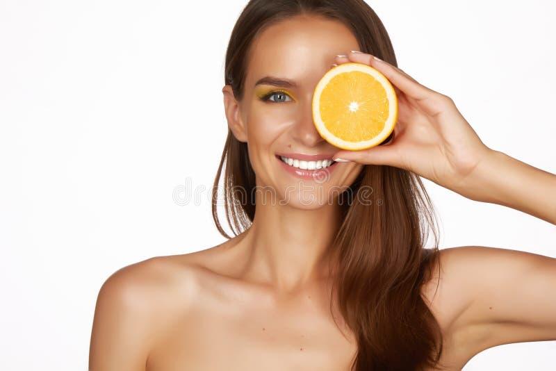Красивая сексуальная женщина брюнет с цитрусом на белой предпосылке, здоровой едой, вкусной едой, органической диетой, усмехается стоковое изображение rf