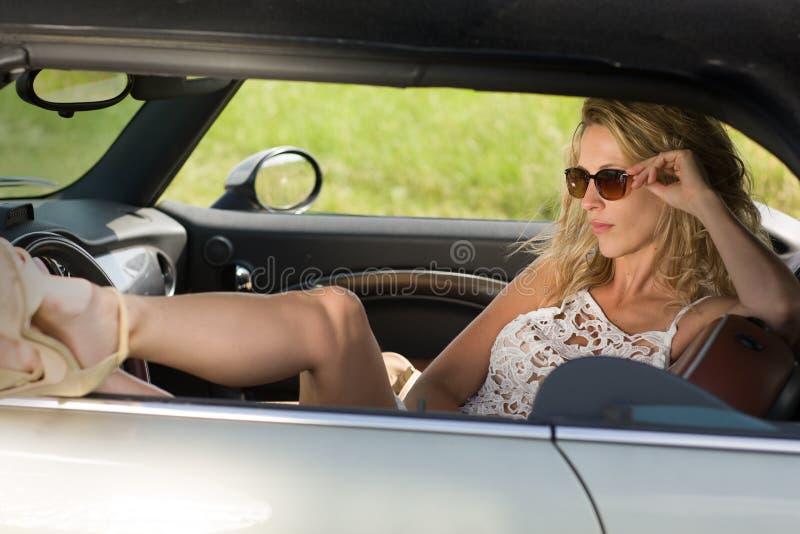 Красивая, сексуальная женщина сидит в автомобиле, белом платье и солнечных очках стоковые фото