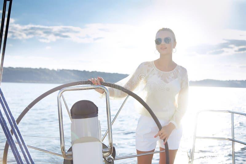 Красивая сексуальная молодая белокурая женщина, ехать шлюпка на воде, распорядок, красивый состав, одежда, лето, солнце, совершен стоковое фото rf