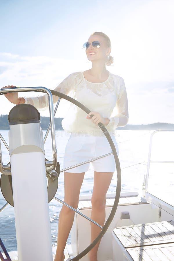 Красивая сексуальная молодая белокурая женщина, ехать шлюпка на воде, распорядок, красивый состав, одежда, лето, солнце, совершен стоковые фотографии rf