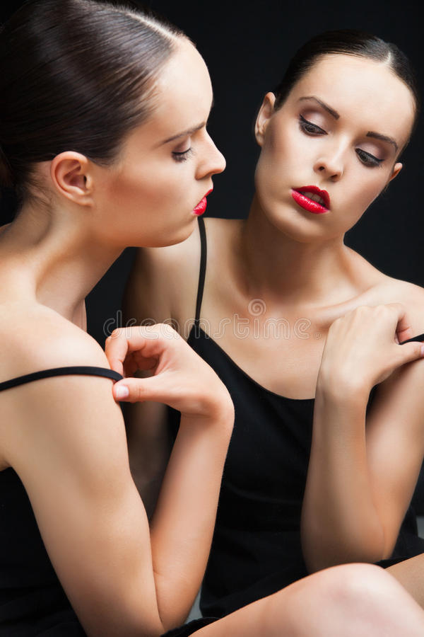 Красивая сексуальная молодая женщина около зеркала над чернотой стоковые изображения