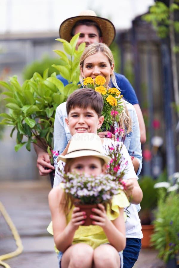 Красивая семья смотря камеру пока держащ цветет в парнике стоковая фотография