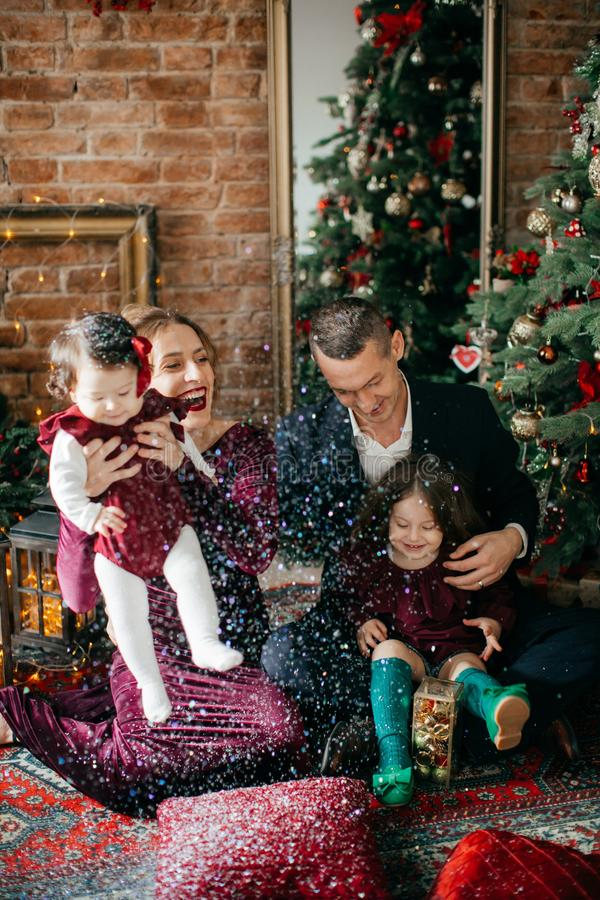 Красивая семья с маленькими девочками около рождественской елки с подарками стоковое изображение rf