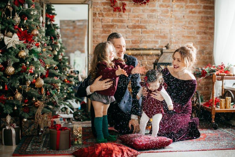 Красивая семья с маленькими девочками около рождественской елки с подарками стоковое фото