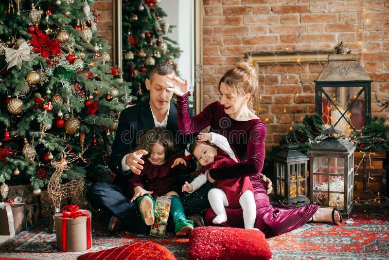 Красивая семья с маленькими девочками около рождественской елки с подарками стоковое изображение