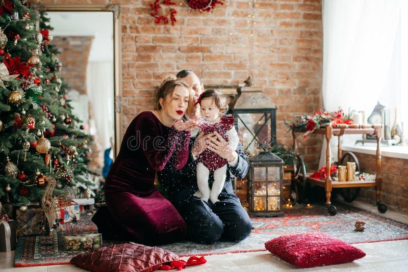 Красивая семья с маленькими девочками около рождественской елки с подарками стоковая фотография