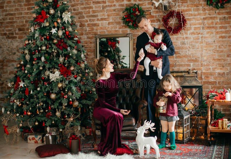 Красивая семья с маленькими девочками около рождественской елки с подарками стоковые фото