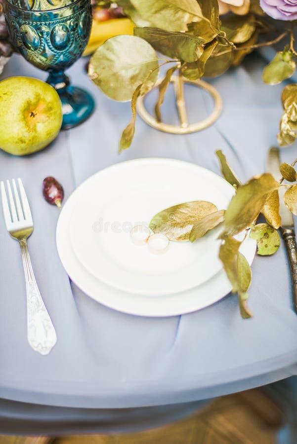 Красивая сервировка стола с посудой и цветками для партии, приема по случаю бракосочетания стоковая фотография rf