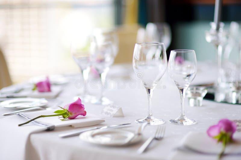 Красивая сервировка стола с посудой и цветками для партии, приема по случаю бракосочетания или другого праздничного события стоковые фото