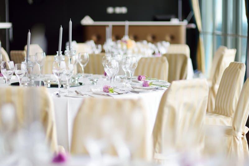 Красивая сервировка стола с посудой и цветками для партии, приема по случаю бракосочетания или другого праздничного события стоковая фотография