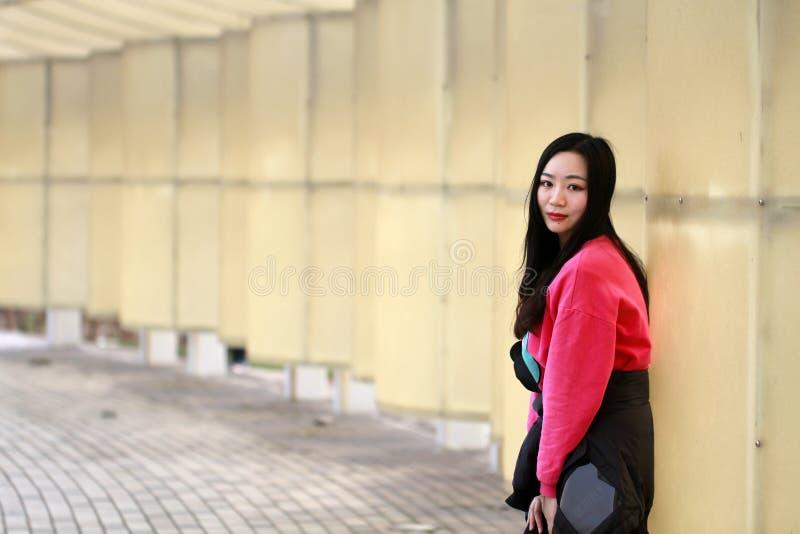 Красивая склонность девушки фарфора против белой загородки стоковое фото rf