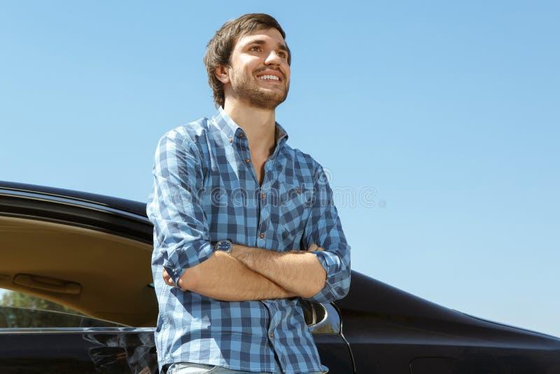 Красивая склонность парня на его автомобиле стоковое изображение rf