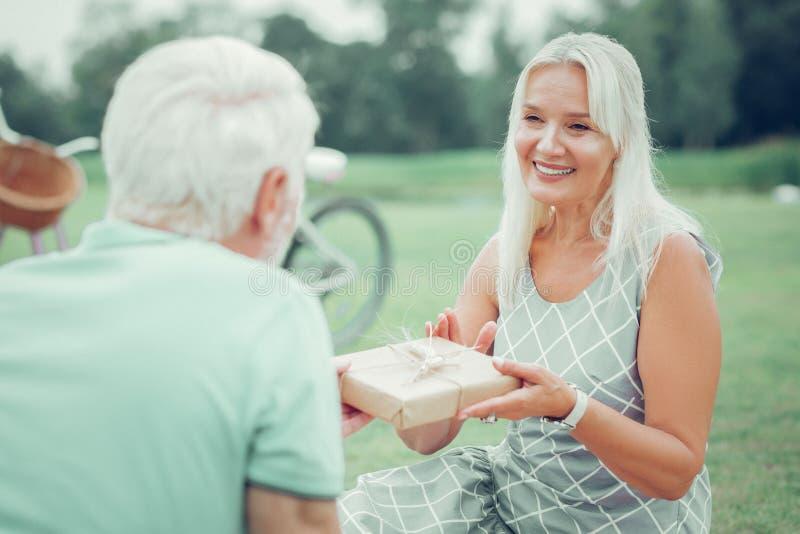 Красивая славная женщина давая настоящий момент ее супругу стоковая фотография