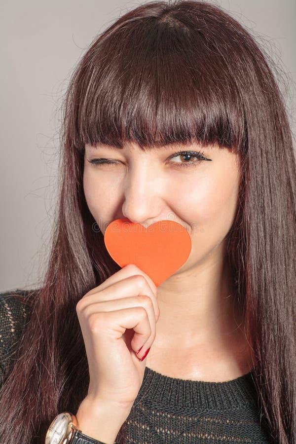 Красивая смешная женщина с вскользь составом и красное сердце в руке стоковое изображение