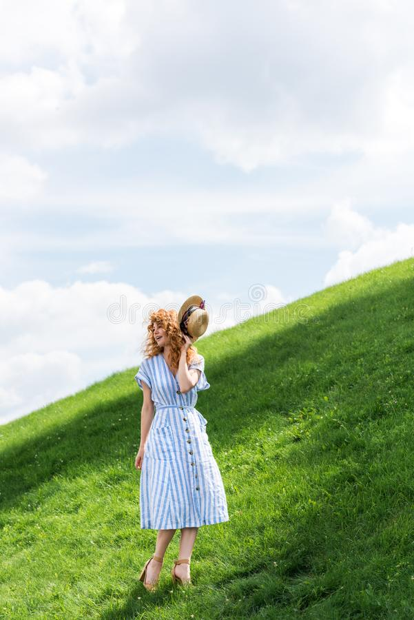 красивая соломенная шляпа удерживания женщины redhead на травянистом стоковые фото