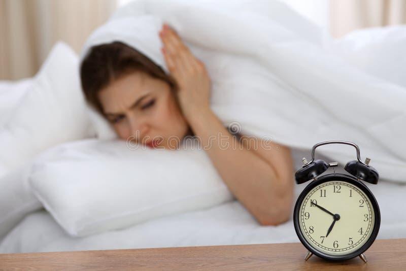 Красивая спать женщина лежа в кровати и пробуя проспать вверх с будильником Девушка имея тревогу с получать вверх раньше стоковая фотография rf