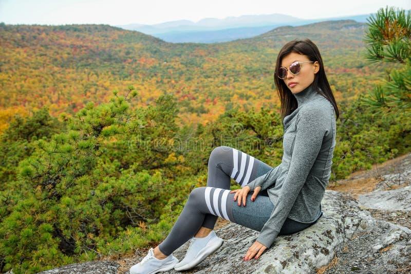 Красивая спортивная молодая женщина, позирующая на вершине горы стоковые фотографии rf