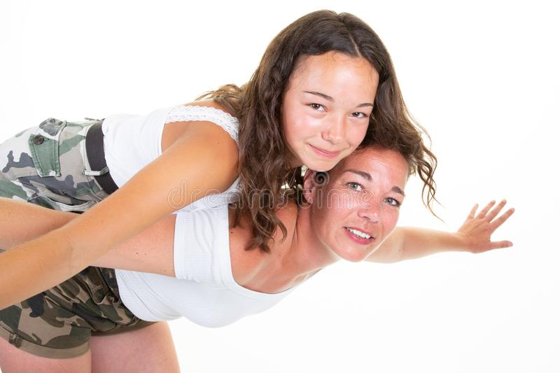 Красивая средне-старинная брюнетка-мать держит на спине милую дочь-подростка в белой изолированной студии на заднем фоне стоковые фото