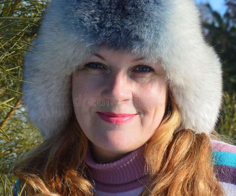 Красивая средн-достигшая возраста женщина идя и смеясь в снежном лесе в зиме стоковые изображения rf