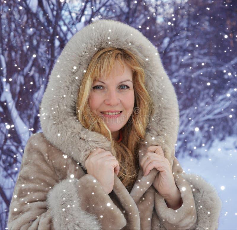 Красивая средн-достигшая возраста женщина идя и смеясь в снежном лесе в зиме стоковая фотография