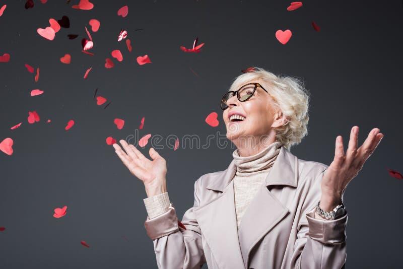 красивая старшая дама с сердцем сформировала confetti на день валентинок st, стоковые фото