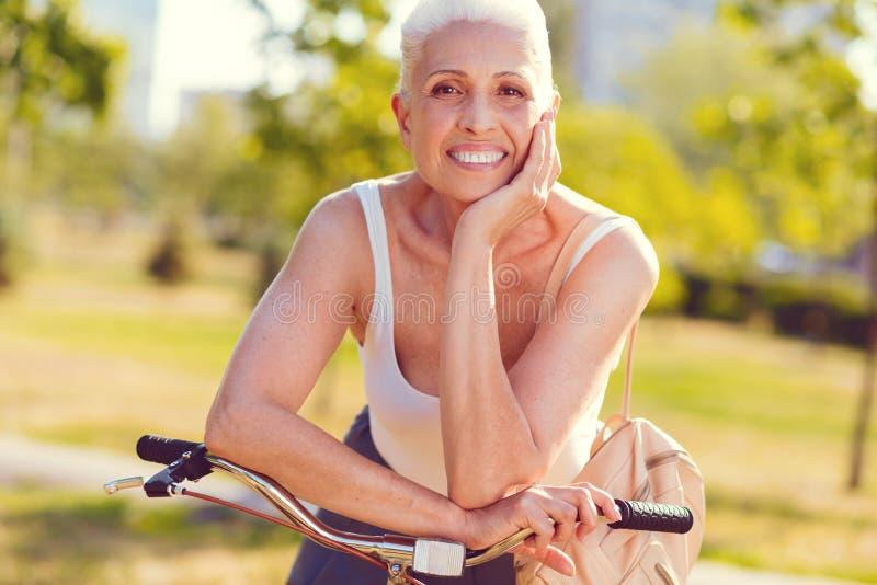 Красивая старшая женщина испуская лучи пока полагающся на велосипеде стоковое фото