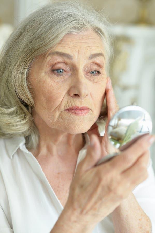 Красивая старшая женщина смотря небольшое зеркало стоковые изображения