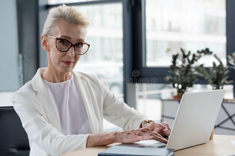 красивая старшая коммерсантка в eyeglasses смотря камеру пока используя ноутбук стоковое фото rf