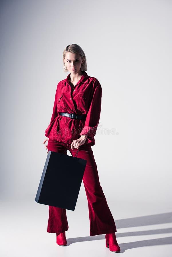 красивая стильная девушка в красных ультрамодных одеждах с хозяйственной сумкой стоковые изображения rf
