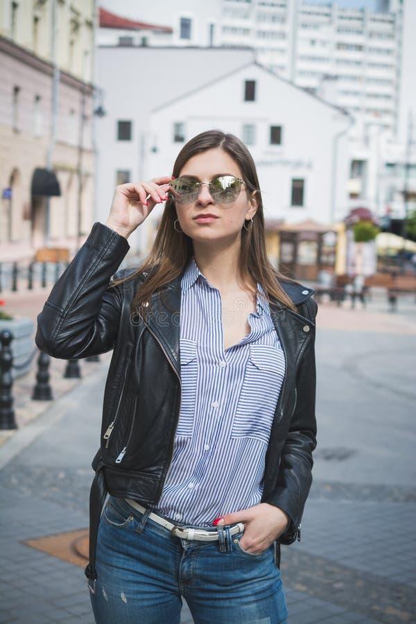 Красивая стильная девушка в черной кожаной куртке, джинсах и солнечных очках стоковое фото