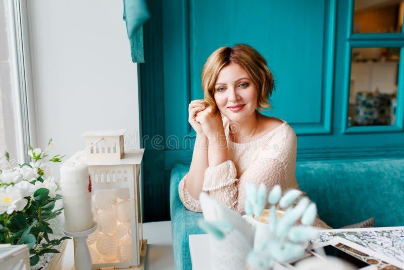 Красивая стильно одетая молодая женщина ослабляет в утре в кафе Ресторан внутренний в голубых цветах _ стоковое фото rf
